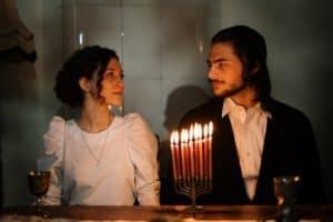 איש ואישה מאחורי חנוכייה עם 8 נרות שעווה דולקים